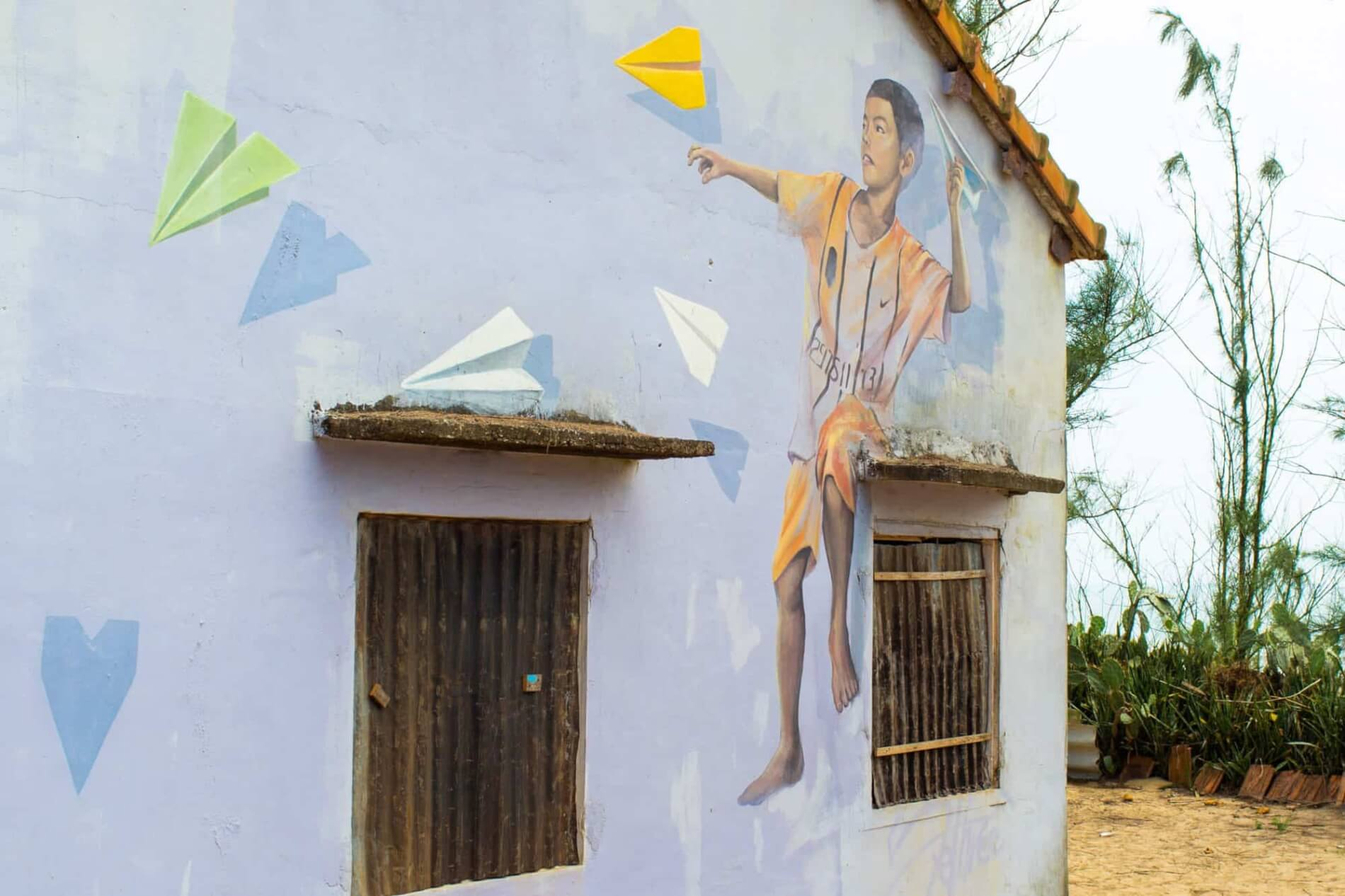 mural of a boy and paper airplanes