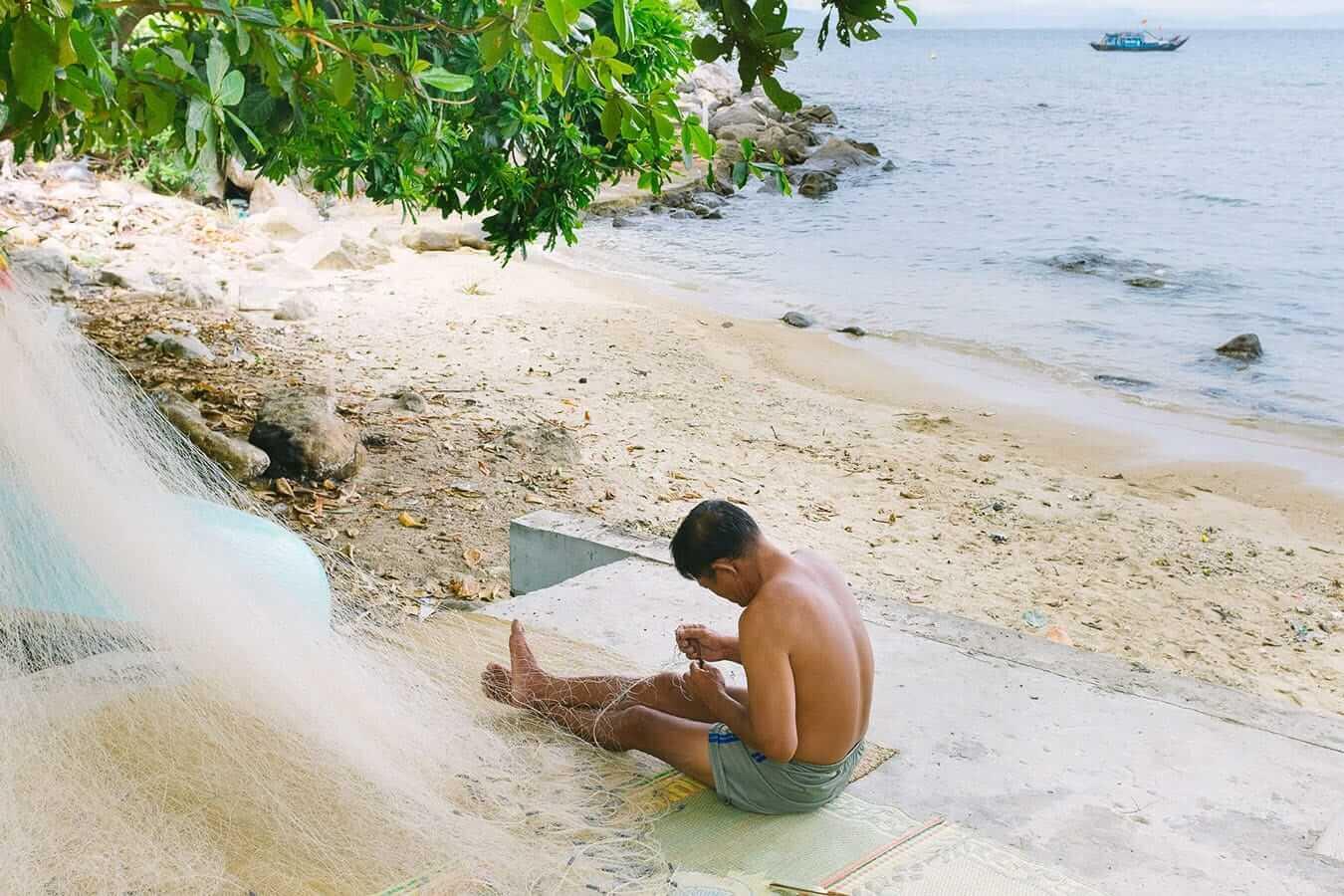 Fisherman repairs net, Cham Islands