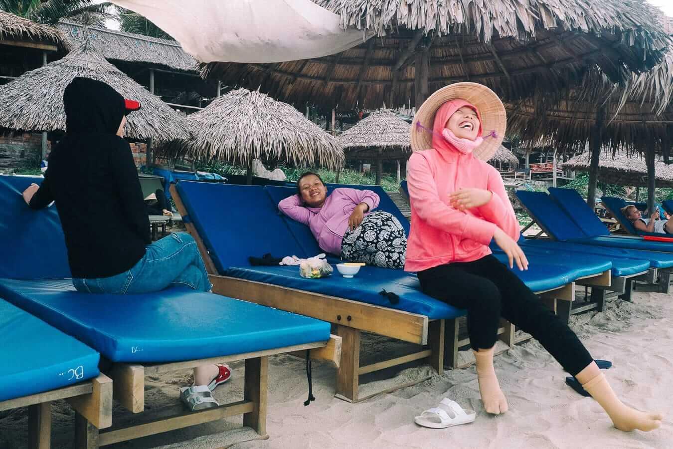 Three Vietnamese ladies on An Bang Beach loungers