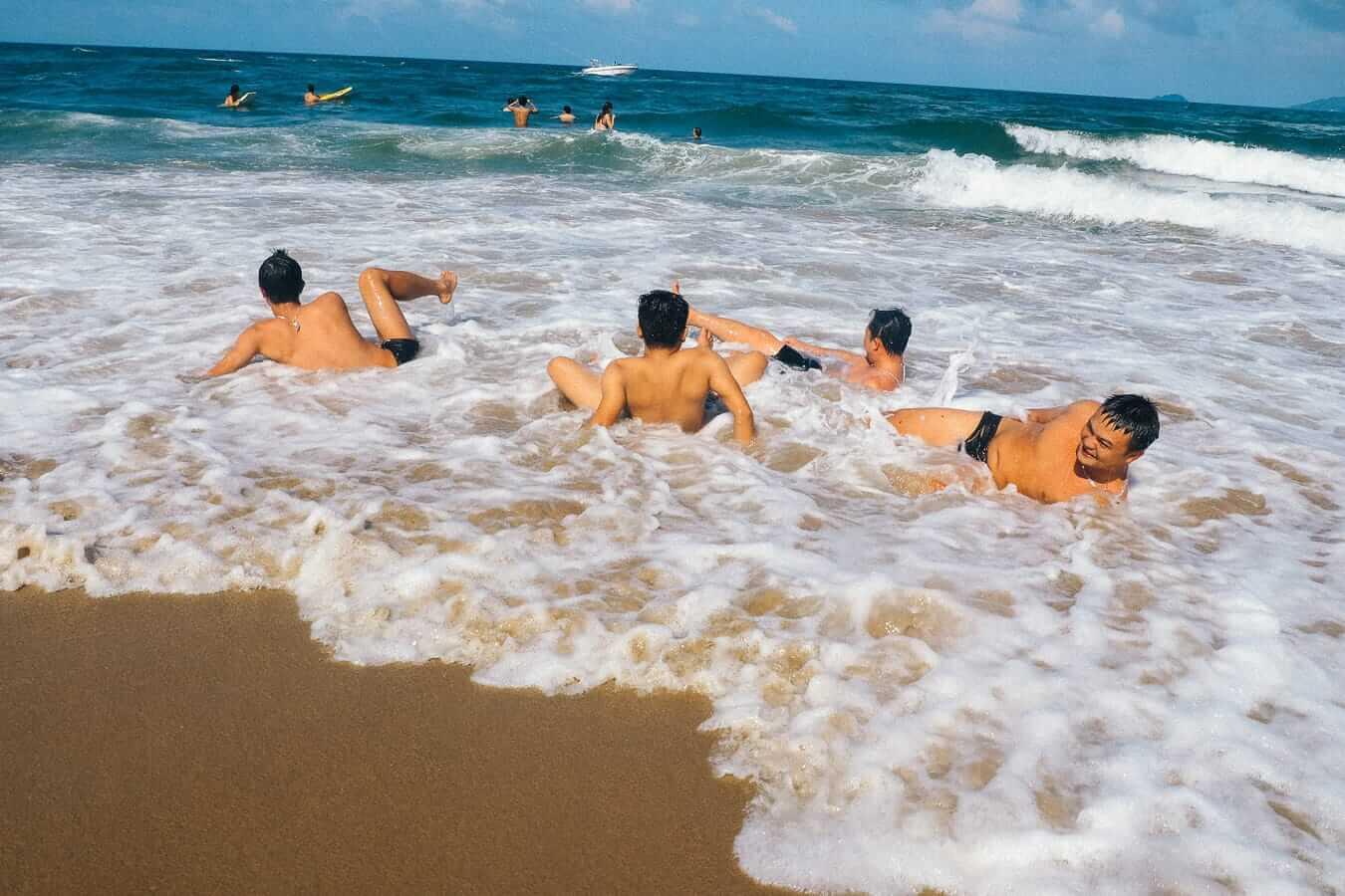 Visitors swimming in An Bang Beach