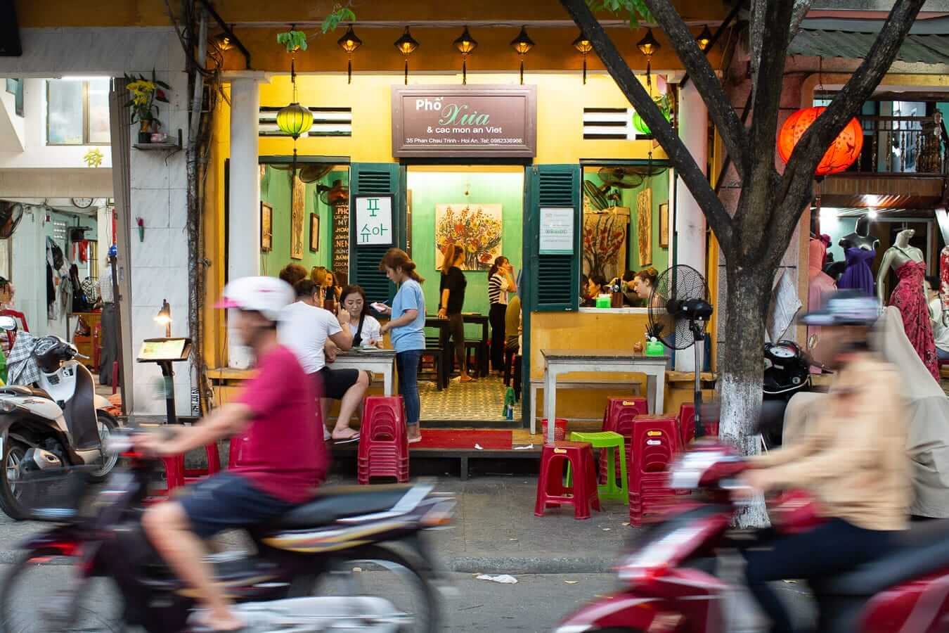 Motorcycles drive past Pho Xua: Best Pho in Hoi An