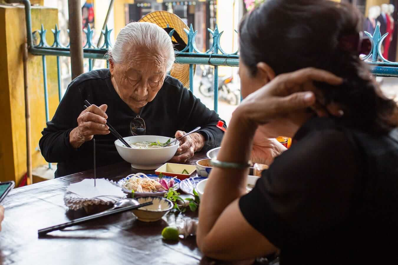 Grandmother and granddaughter having breakfast at Pho Lien: Best Pho in Hoi An