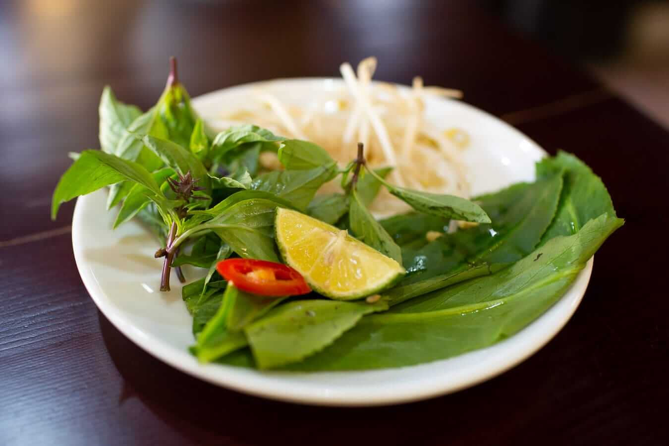Side plate of herbs, lime, chilli, and bean sprouts: Best Pho in Hoi An