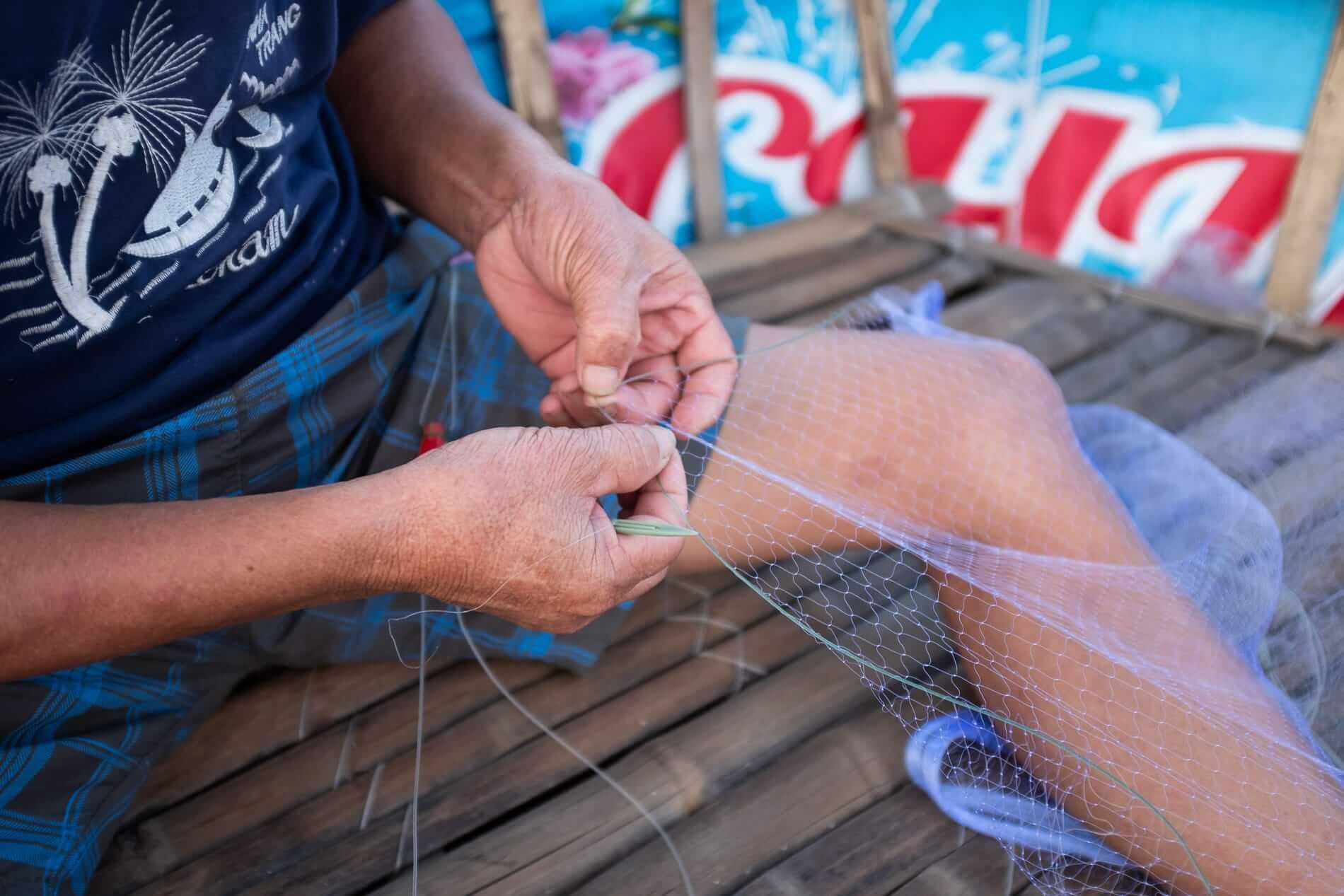 A fisherman repairs his net - Hidden Beach