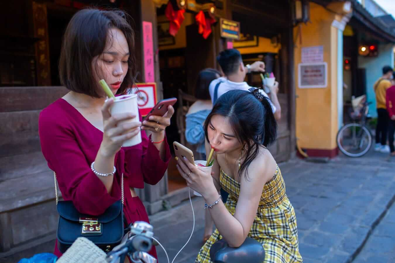 Girls updating their Instagram - Instagram Guide to Hoi An