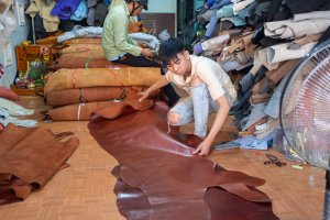 Man cutting sheets of leather