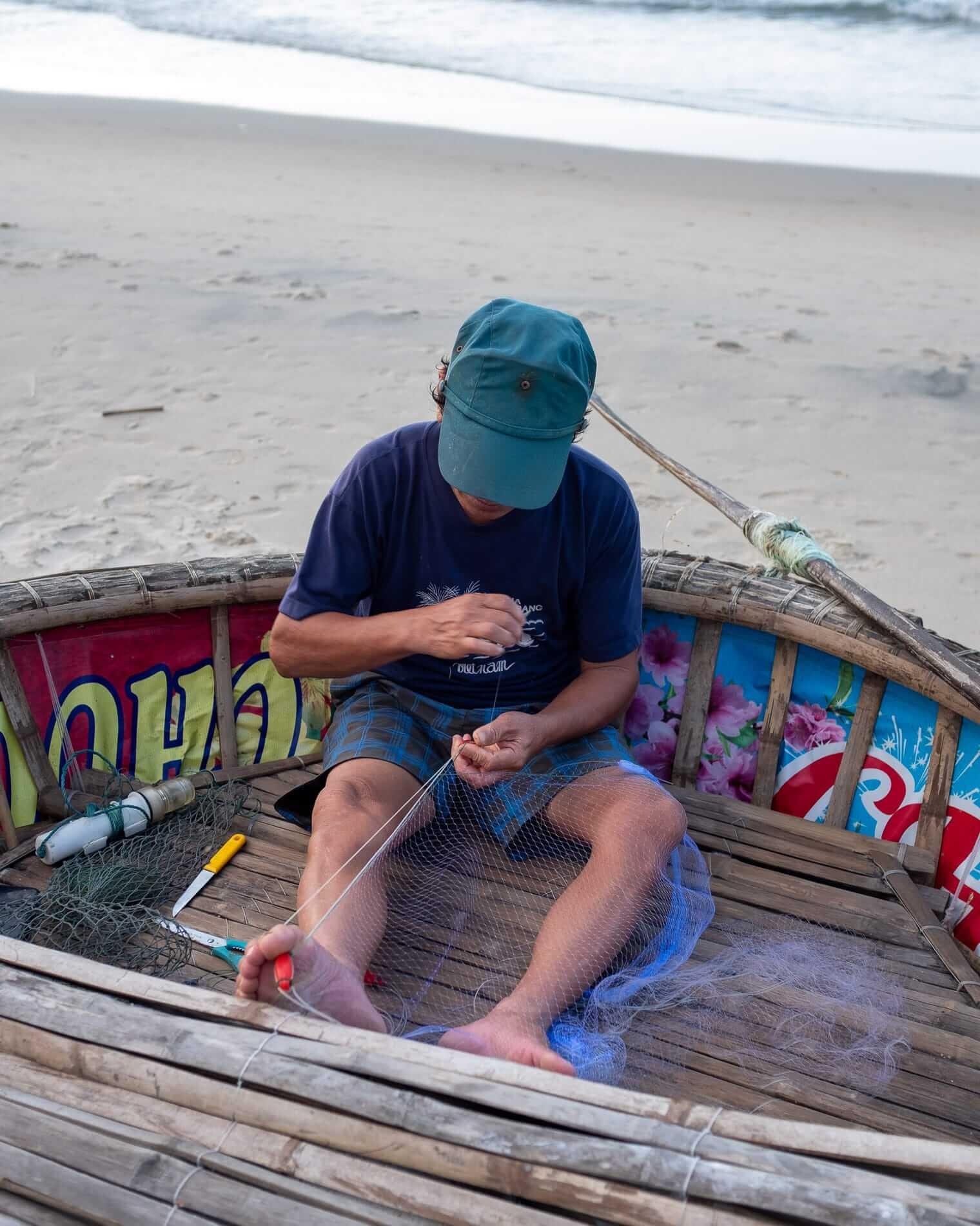 a fisherman repairing his net