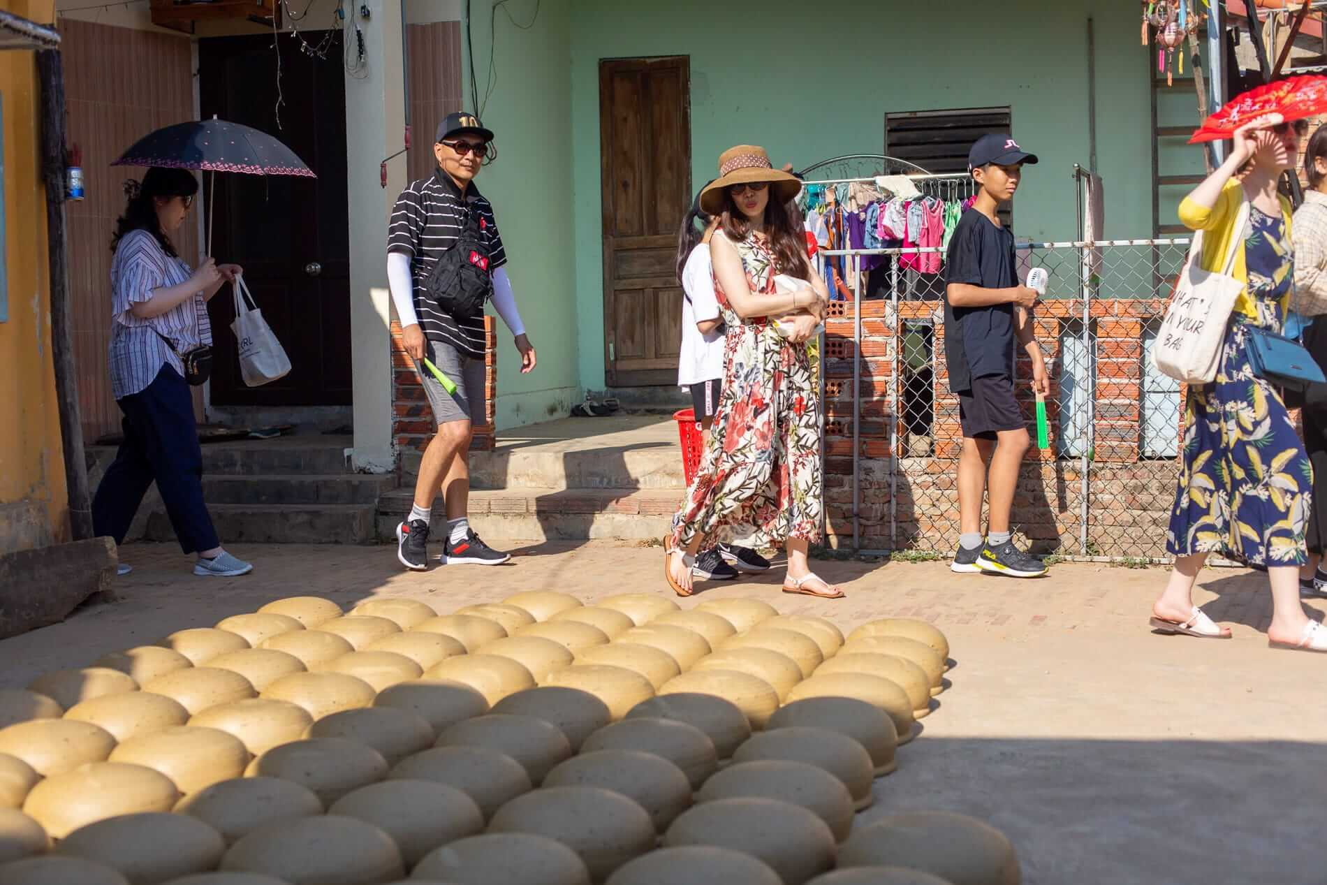 Visitors walk past clay pots - Pottery Village
