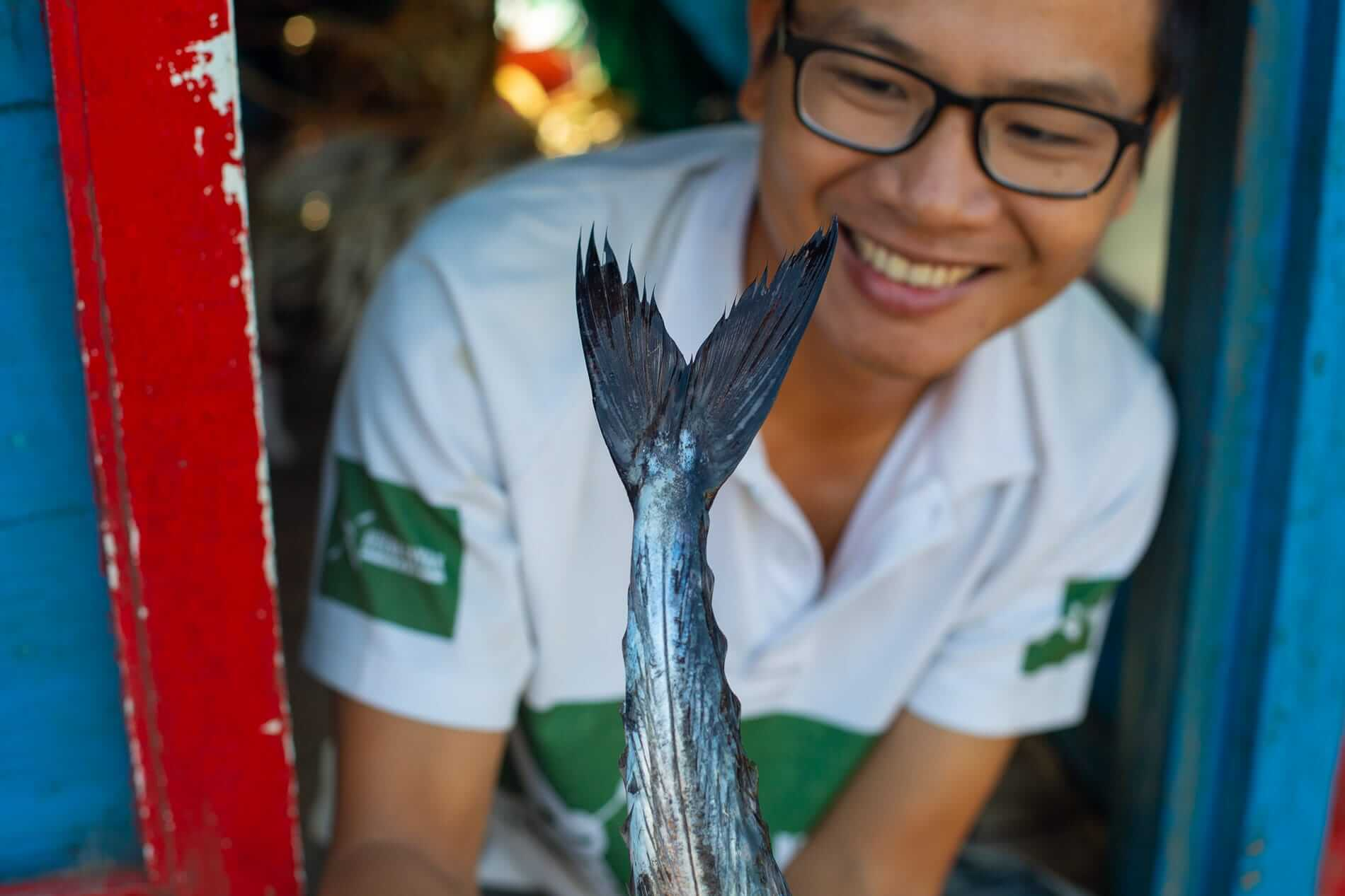Kien holding a fish at the fish market - What to do in Hoi An