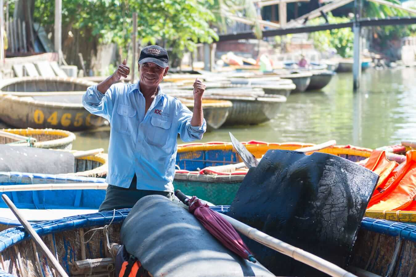 A Vietnamese man gives a thumbs up from his conical boat