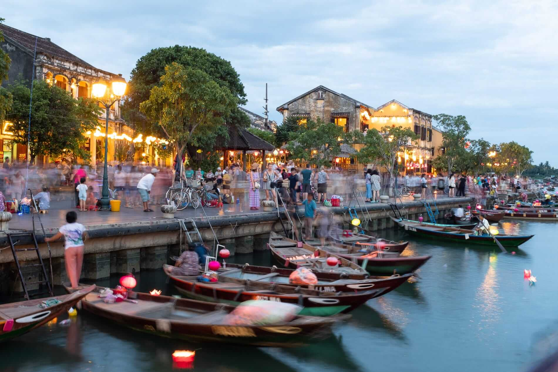 Visitors and boat operators at dusk in Hoi An