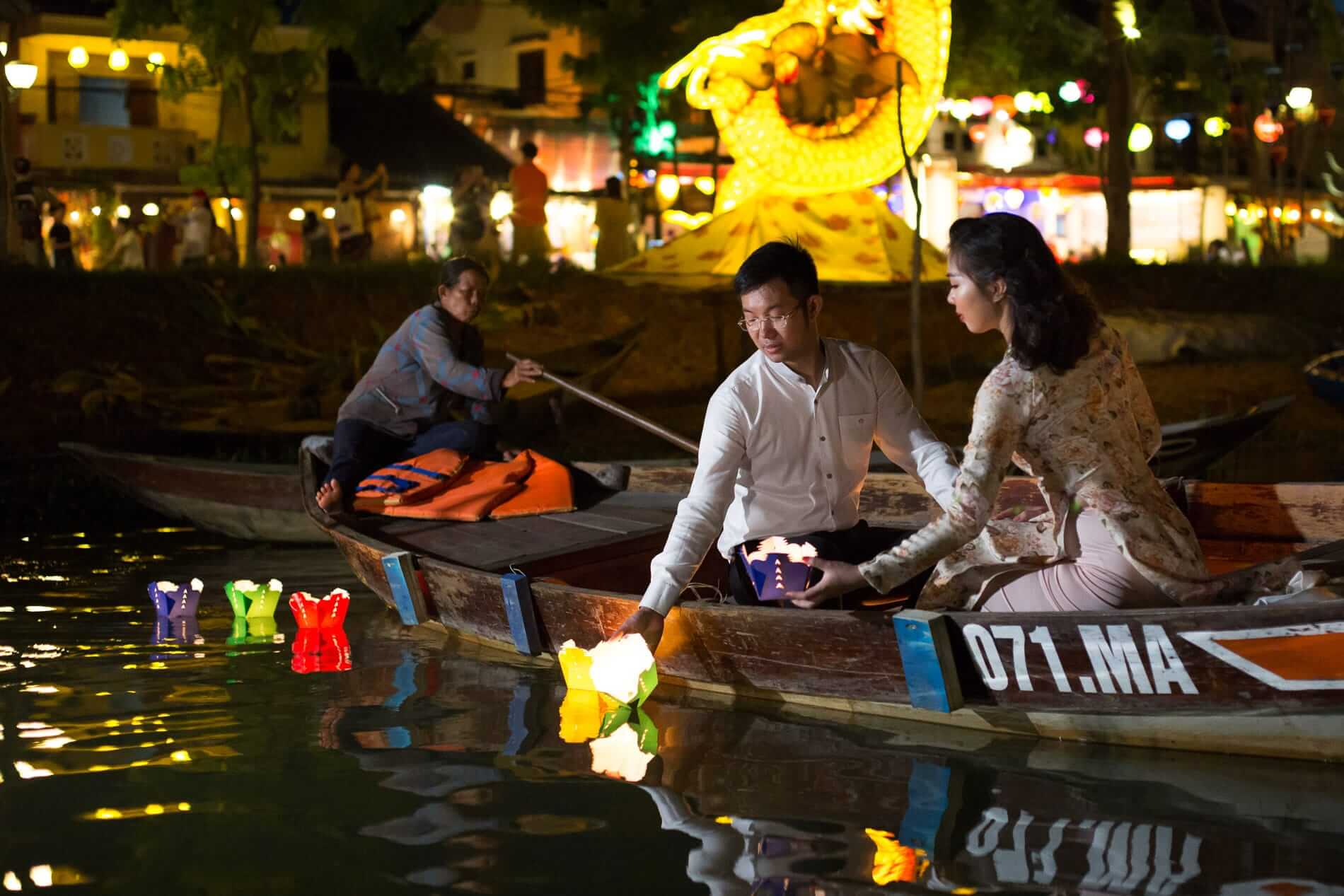 A couple floats traditional lanterns on the river in Hoi An