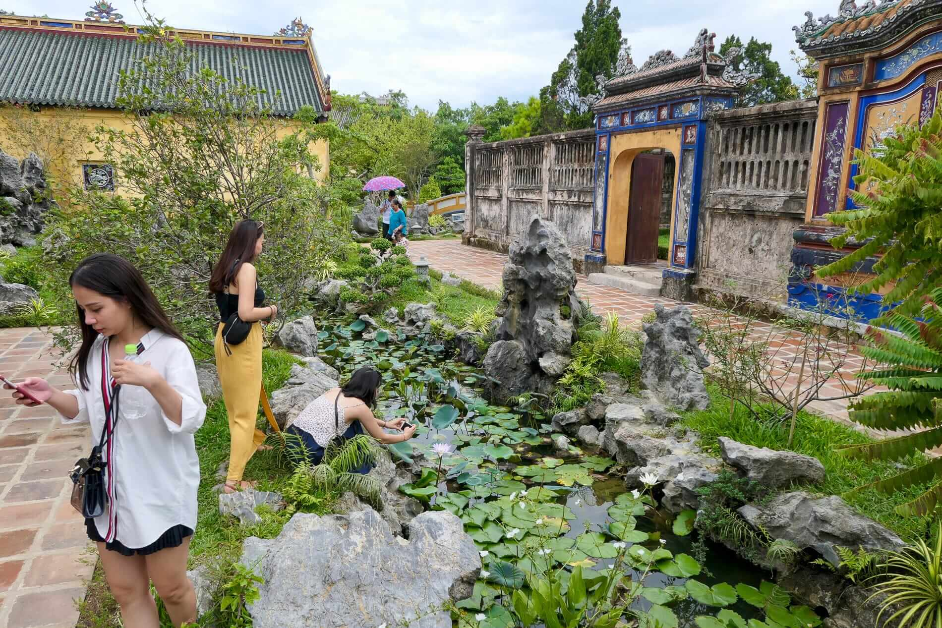 Visitors enjoy the gardens of Hue's ancient buildings