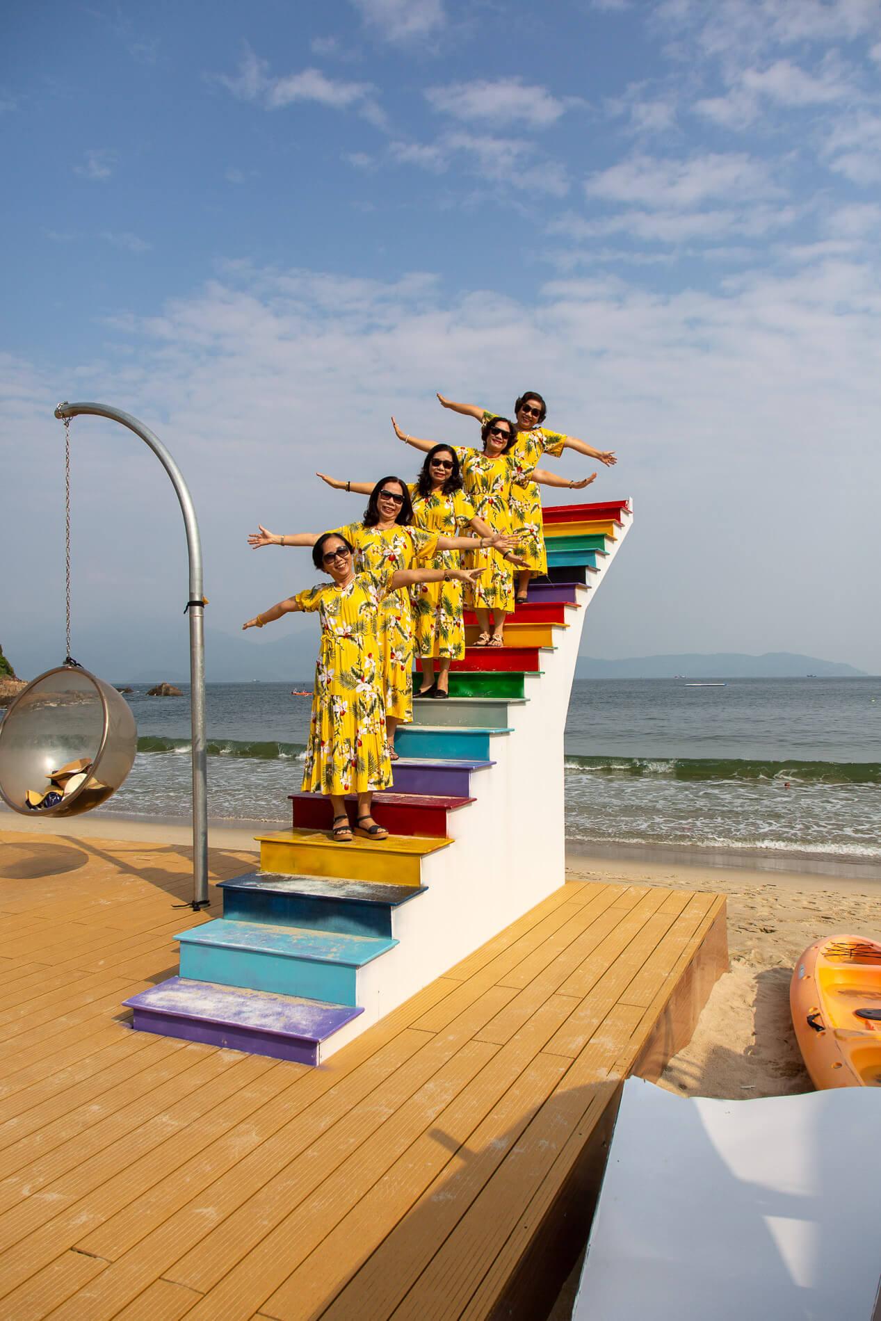Vietnames ladies in matching dresses pose for photos on Bai Bien Tien Sa Beach
