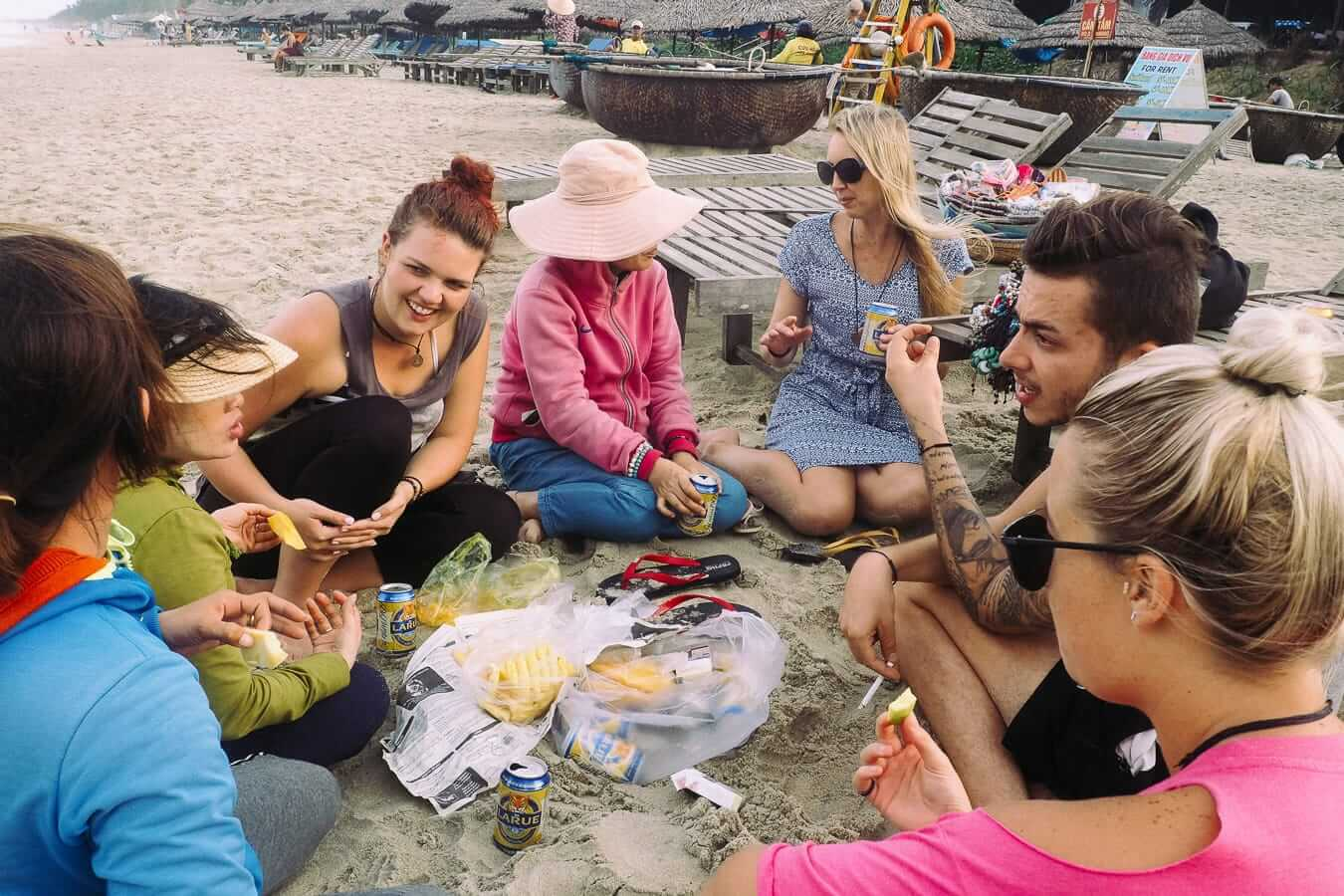 A group of backpackers sharing food and drinks on the beach