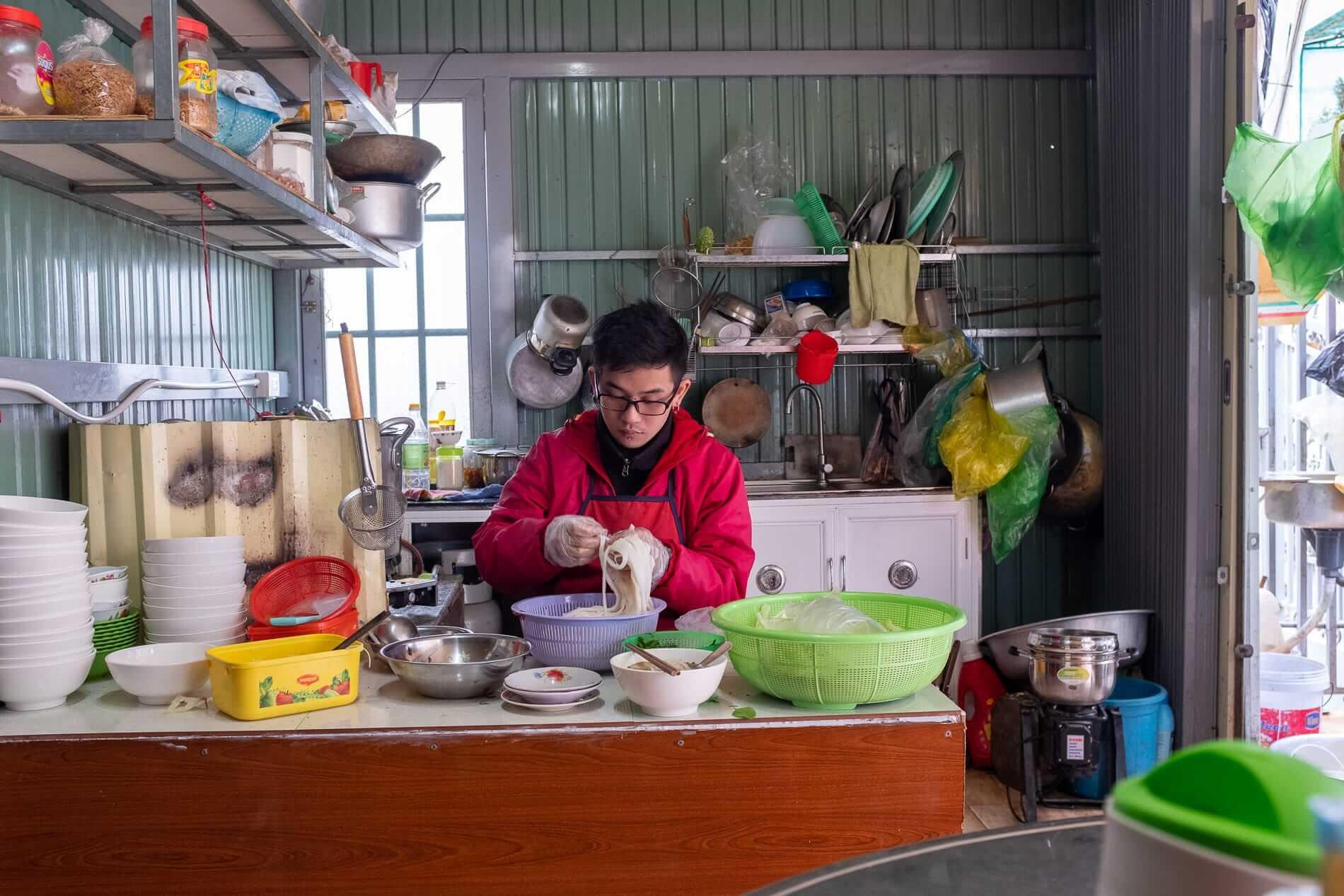 a staff at Duc Loi prepare noodles