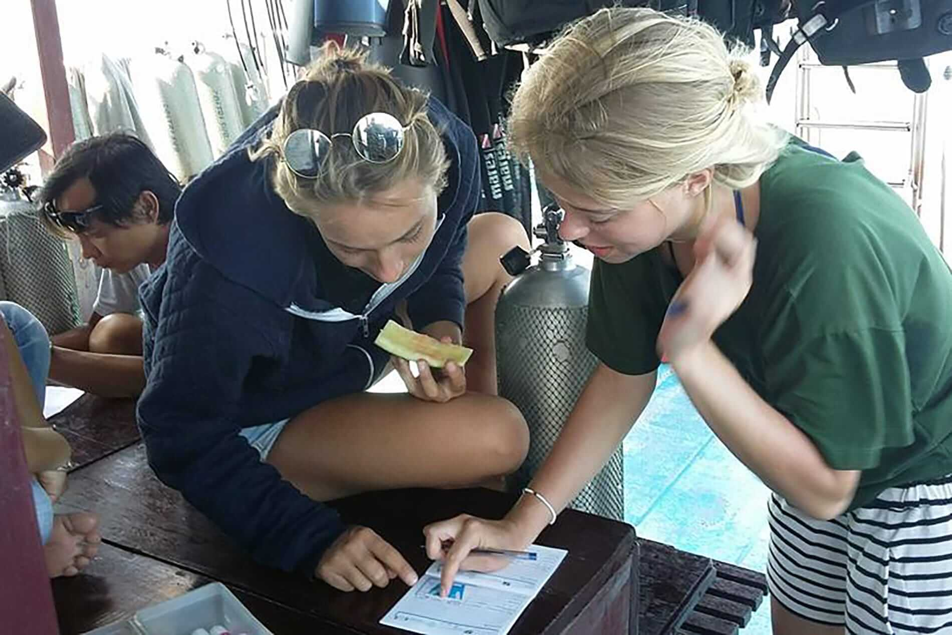 Instructors help diving students to complete dive certification