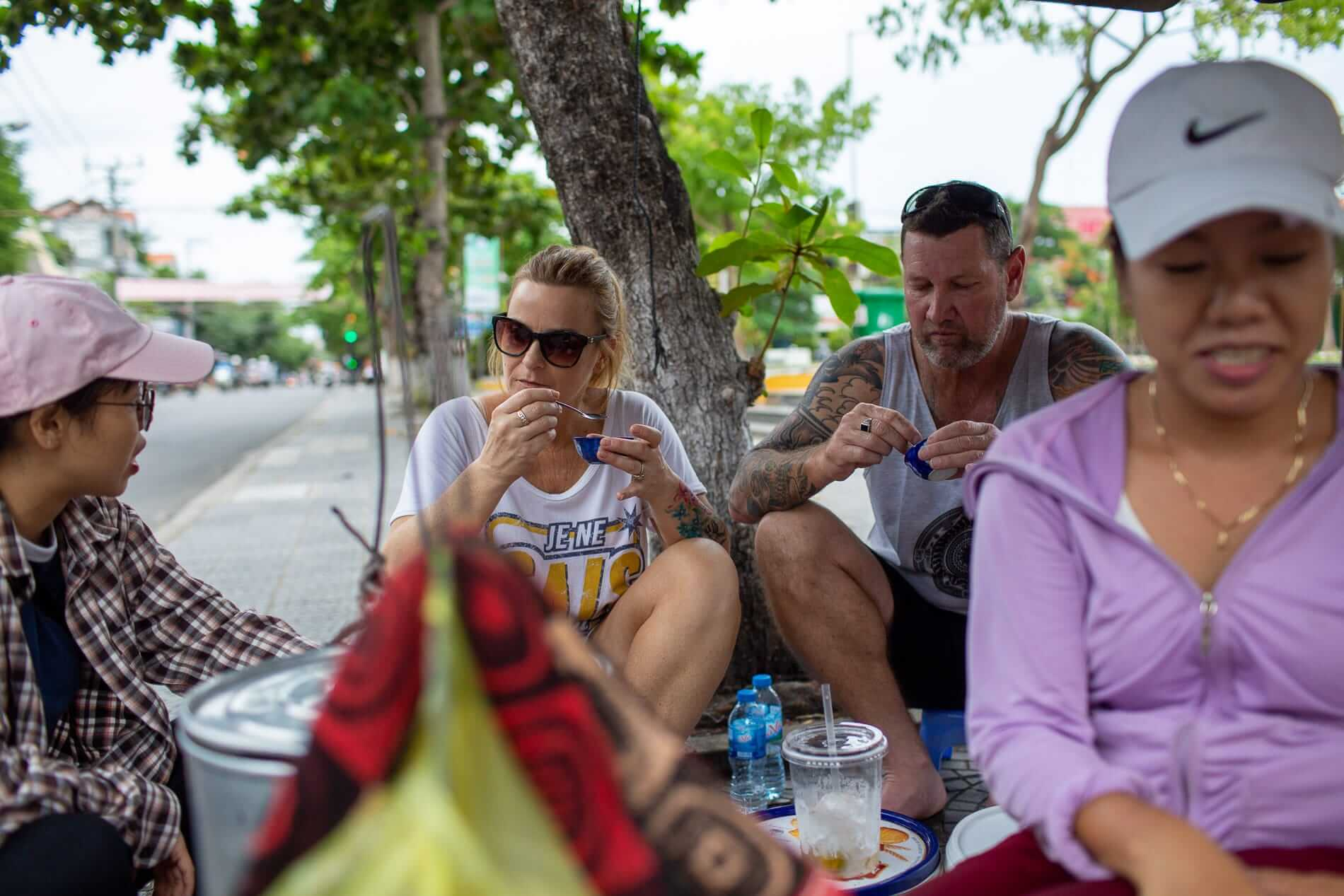 travelers in Hoi An tasting food on their tour