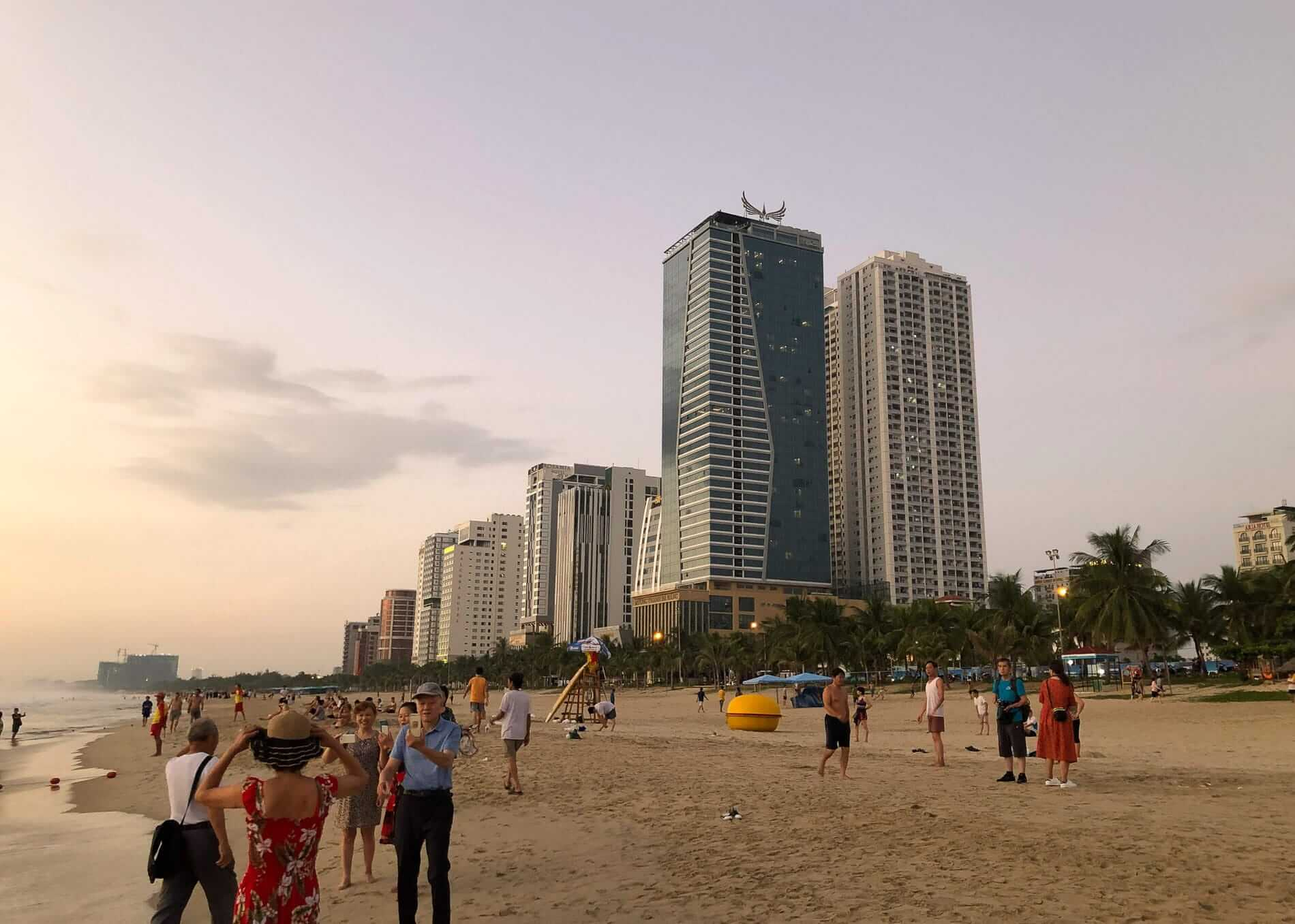 Tourists taking photos in front of beachfront hotels