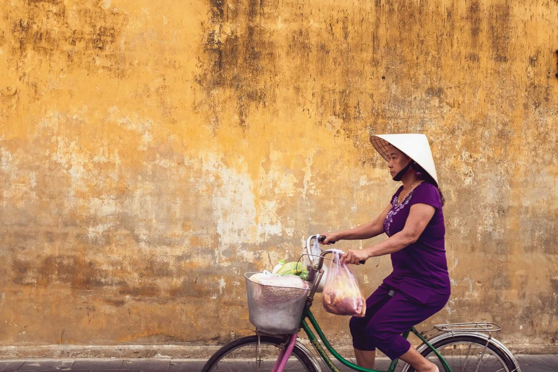 A woman cycling while carrying her shopping