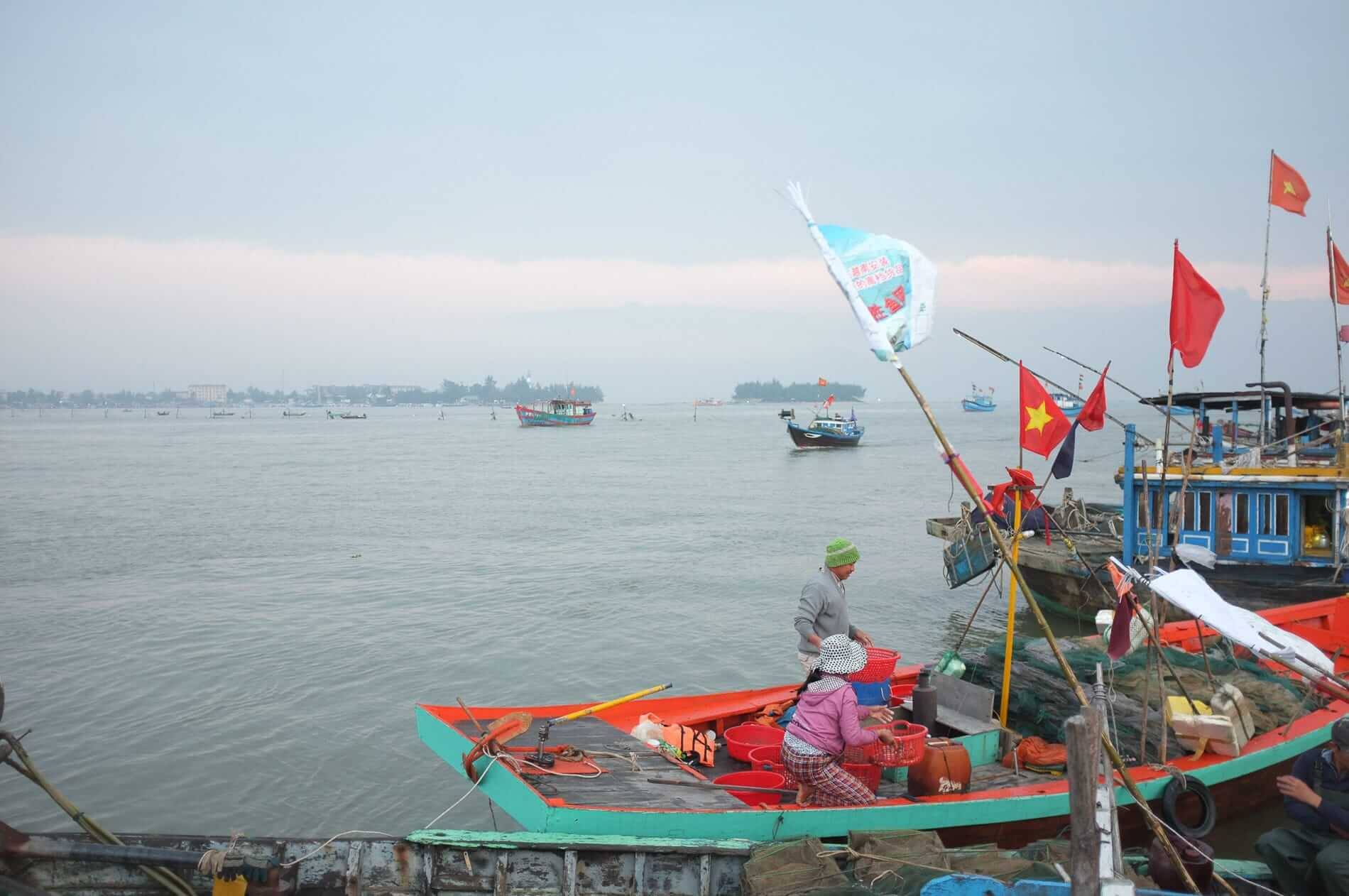 the best time to visit Hoi An is when Vietnamese boats showcase their flagss
