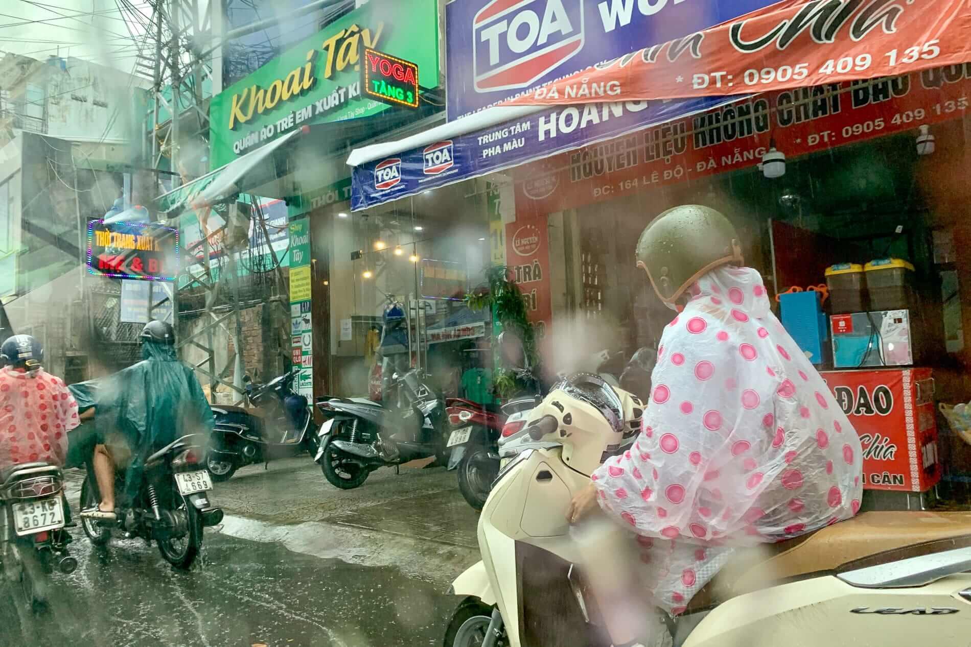 Motorbikes drive through the rain in Da Nang