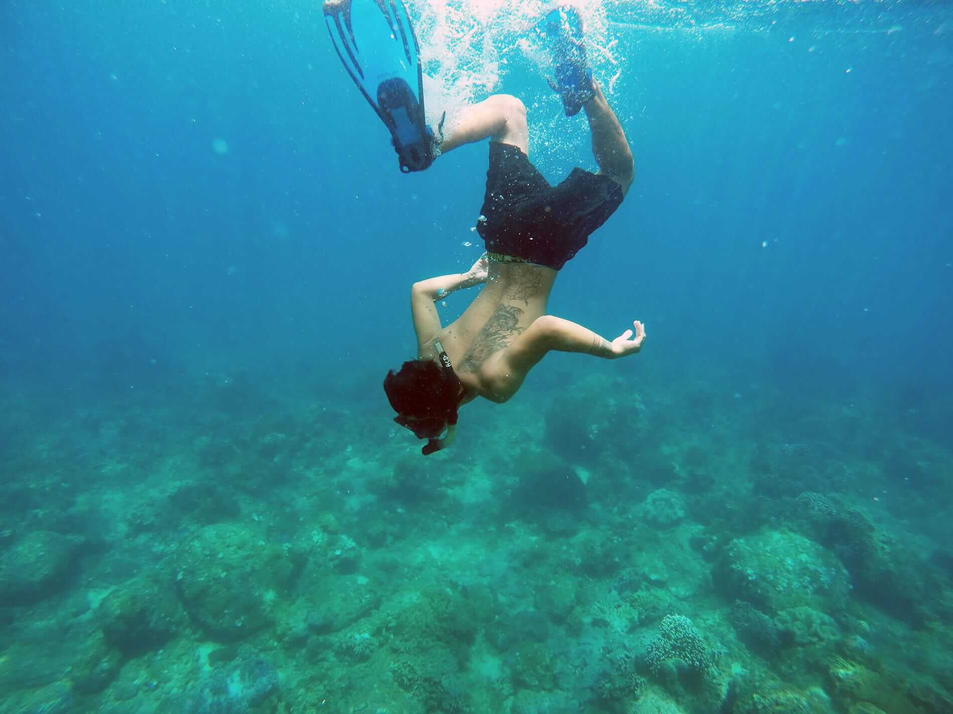 A snorkeller dives under the beautiful ocean of the Cham Islands