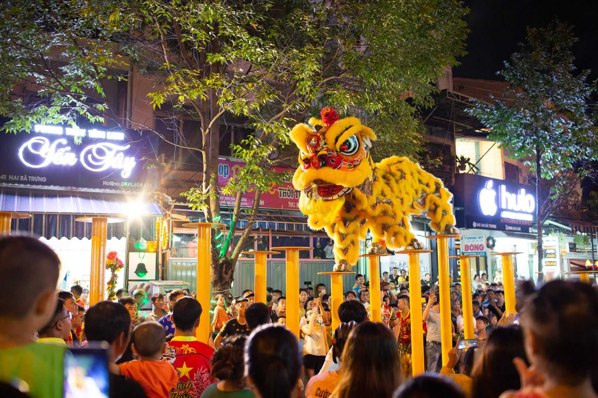 best time to visit Hoi An shows tourists watching a lion dance troupe performer