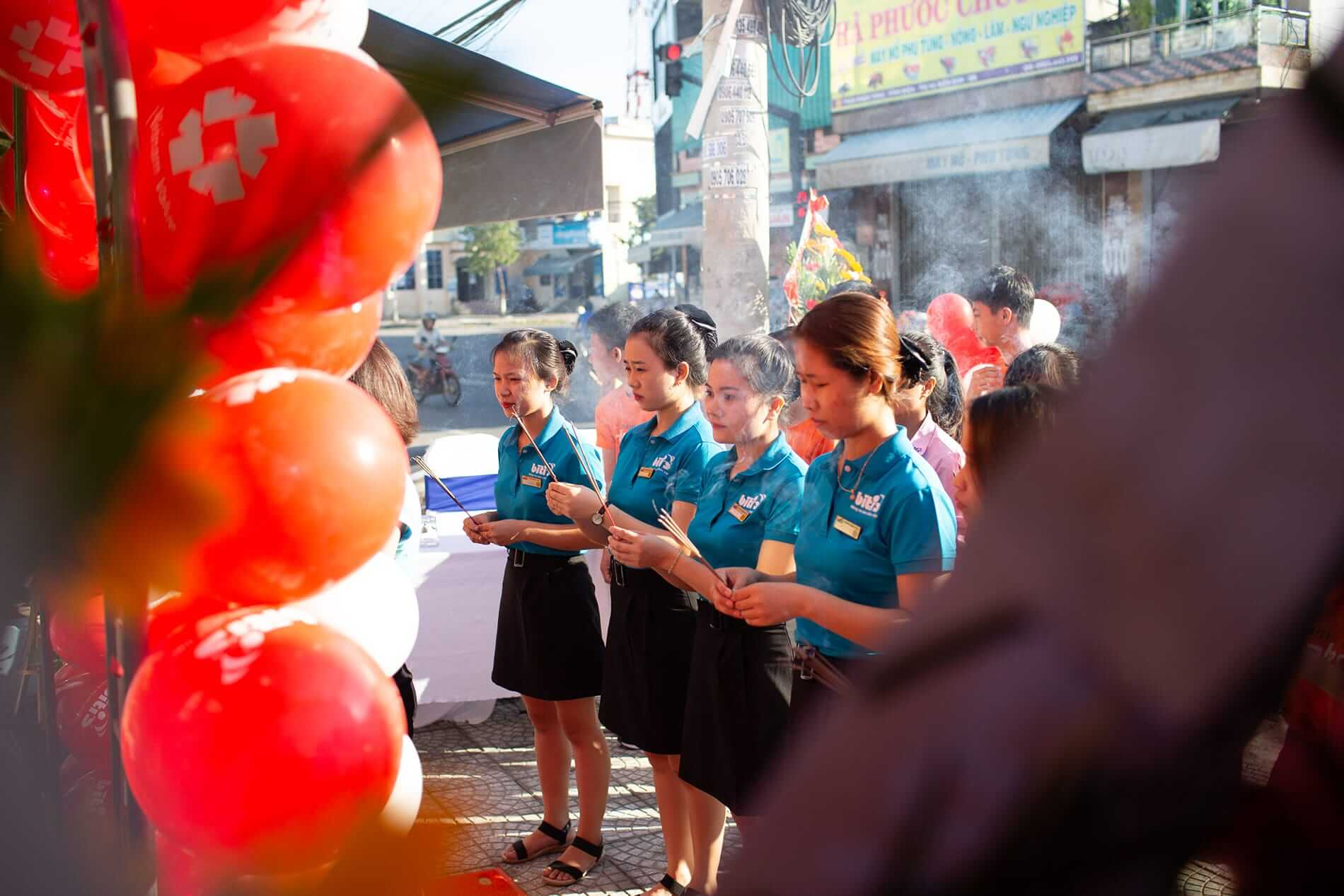 Shop workers light incense during the mid autumn festival