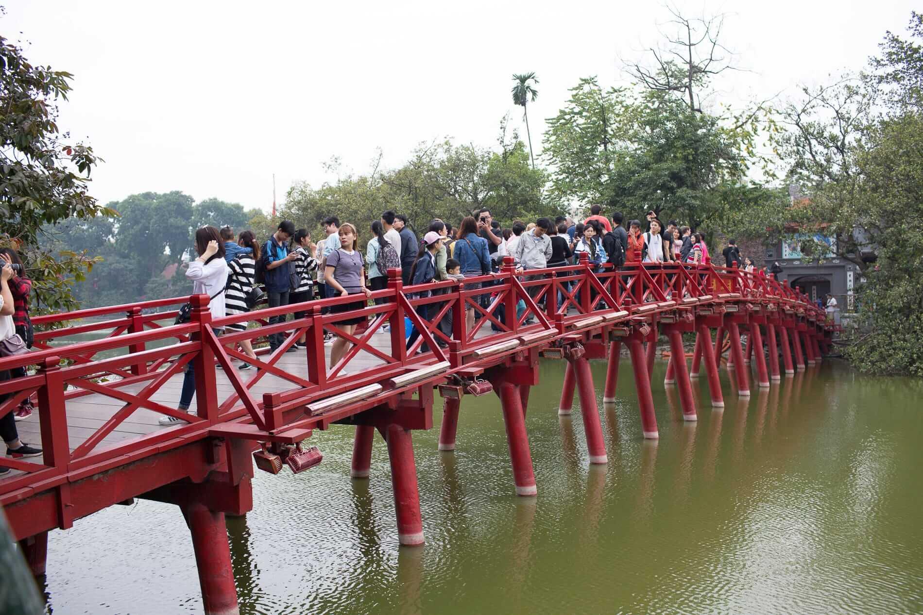 travelers on the little red bridge on Hoan Kiem Lake