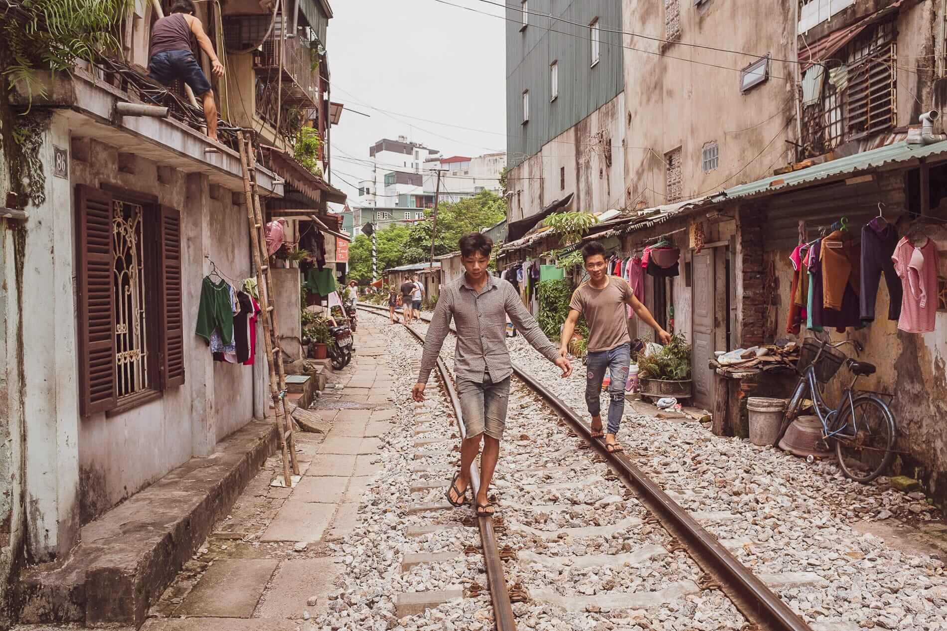 teens walking on train tracks in Hanoi