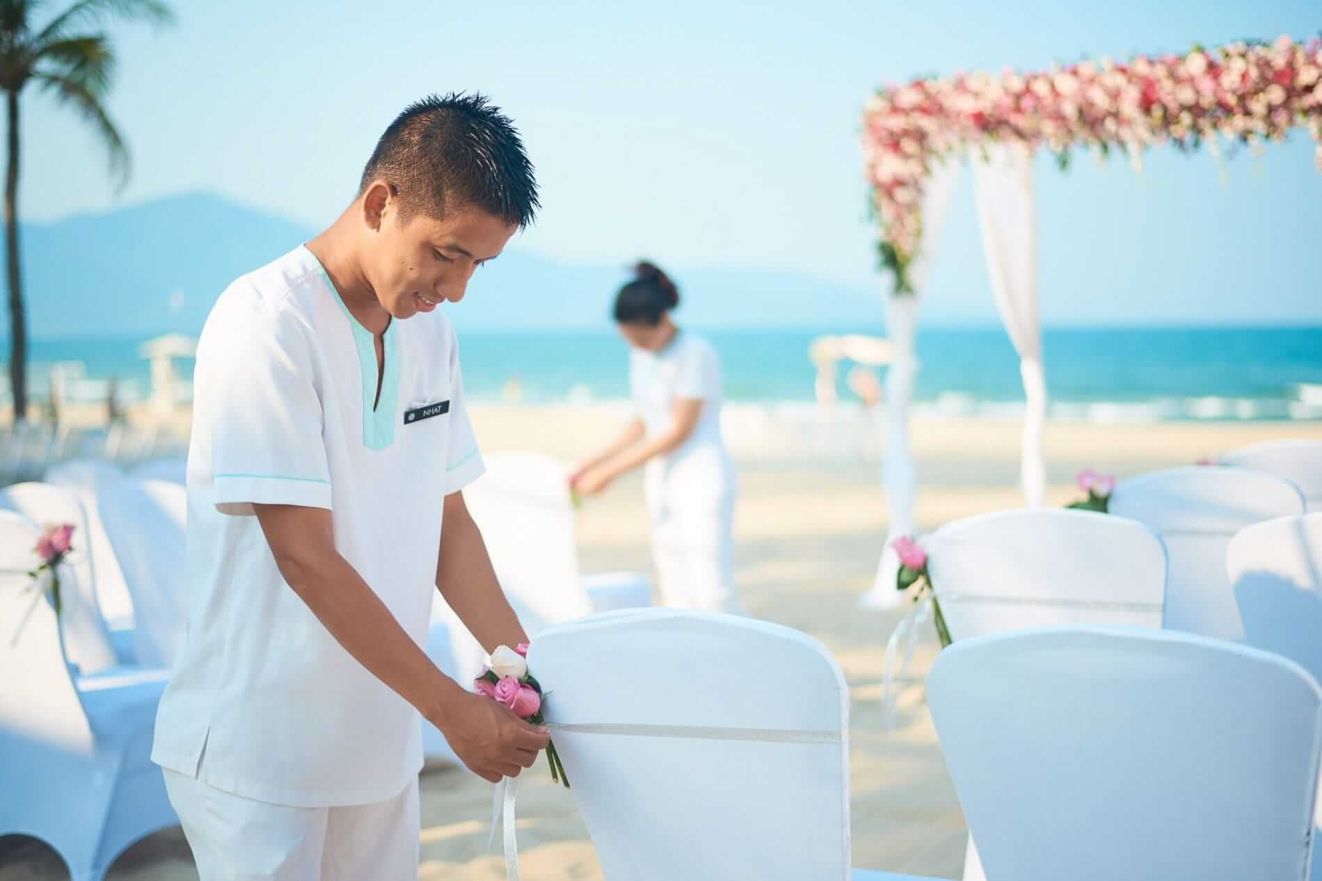 Staff prepares for a wedding at the beach