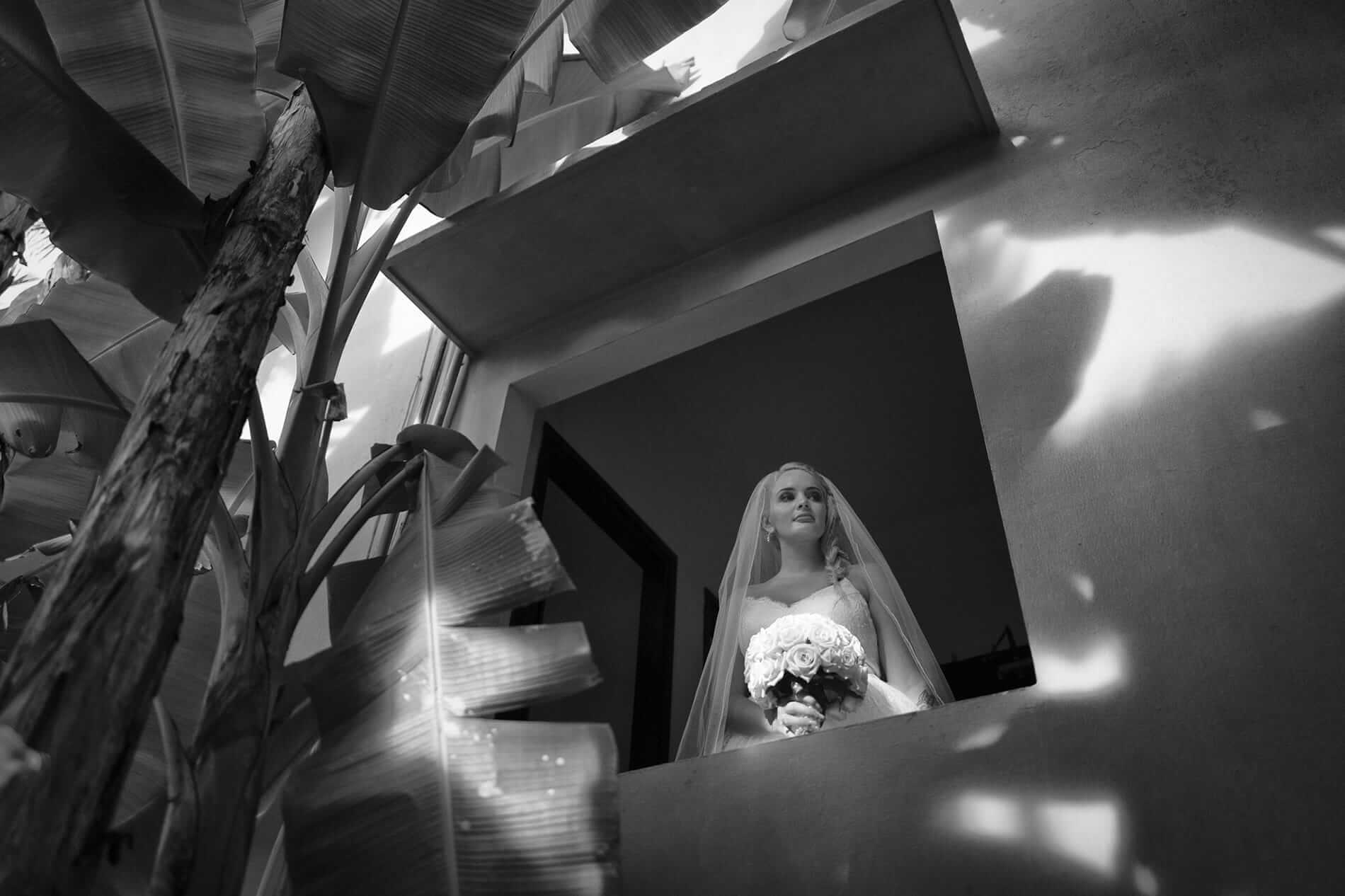 A bride looks over an open window