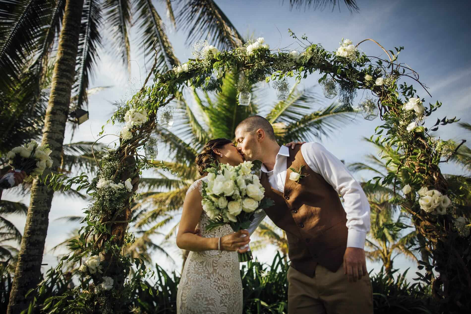A wedding couple kiss behind a flower arch
