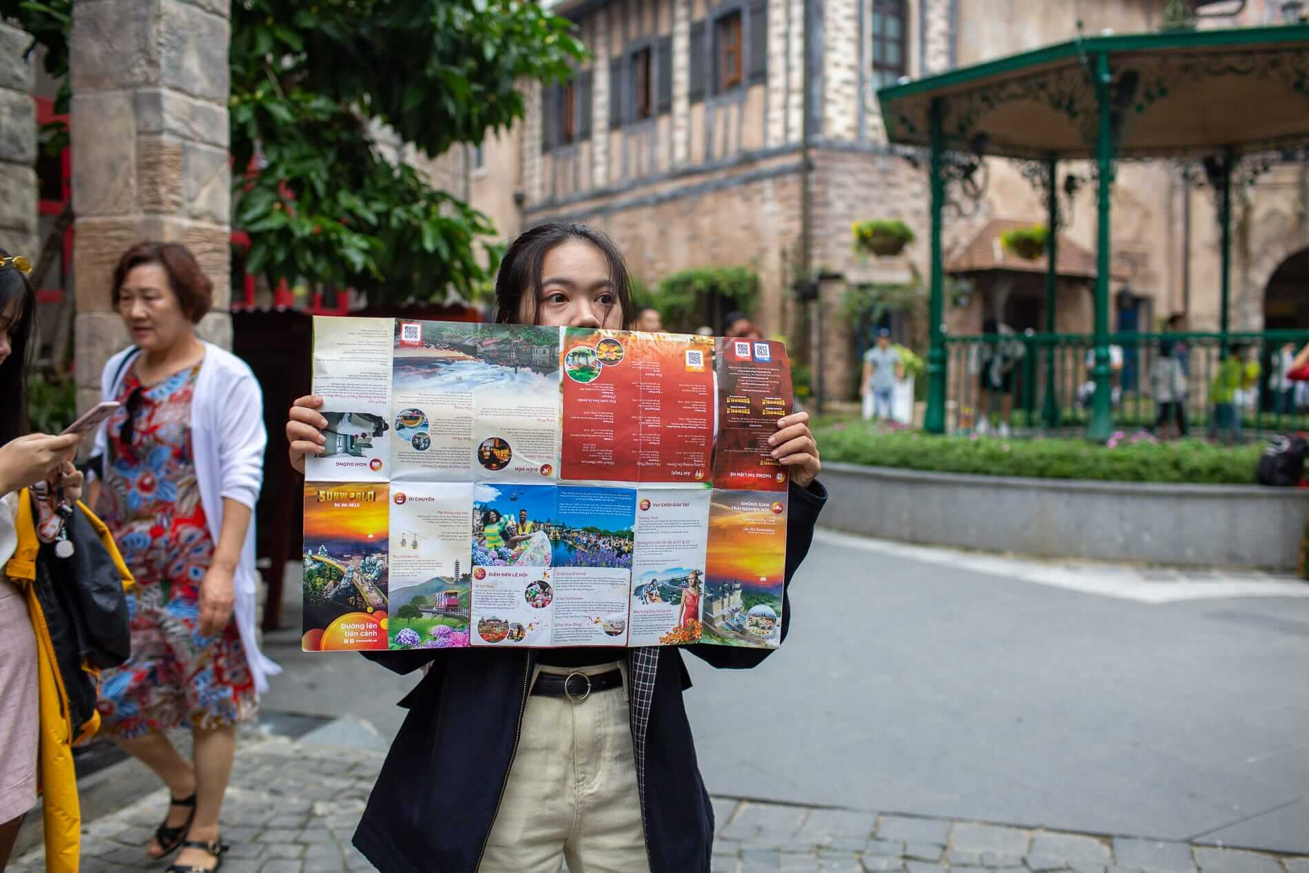 A girl holds a map of Ba Na Hills