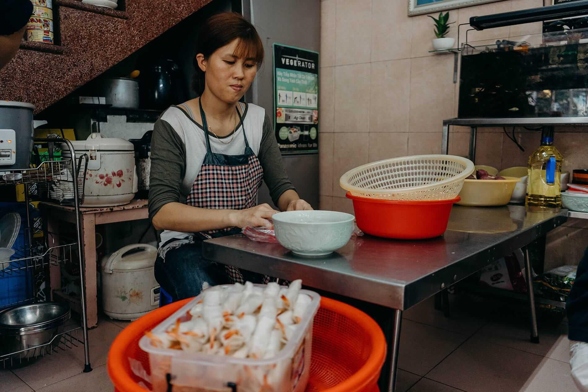 A local woman wraps shrimps in rice paper