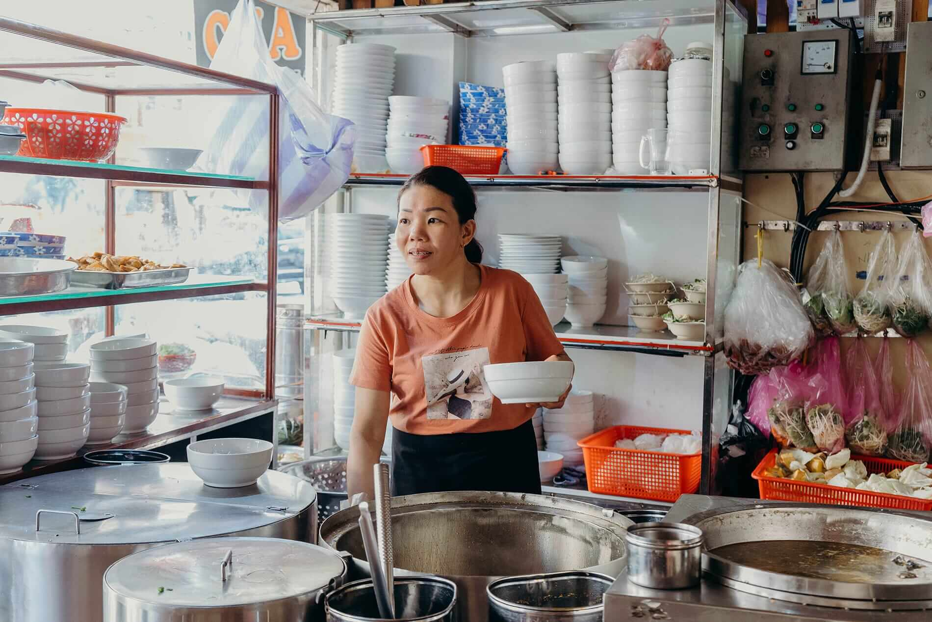 Vendor greets customers in her restaurant