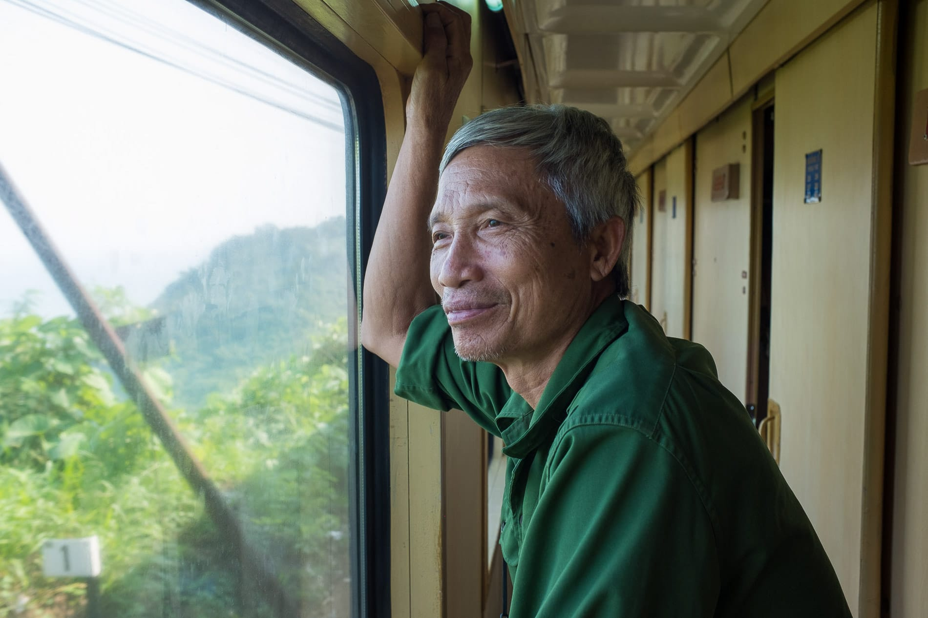 A passenger look out a the scenery from his train ride from Hanoi to Da Nang