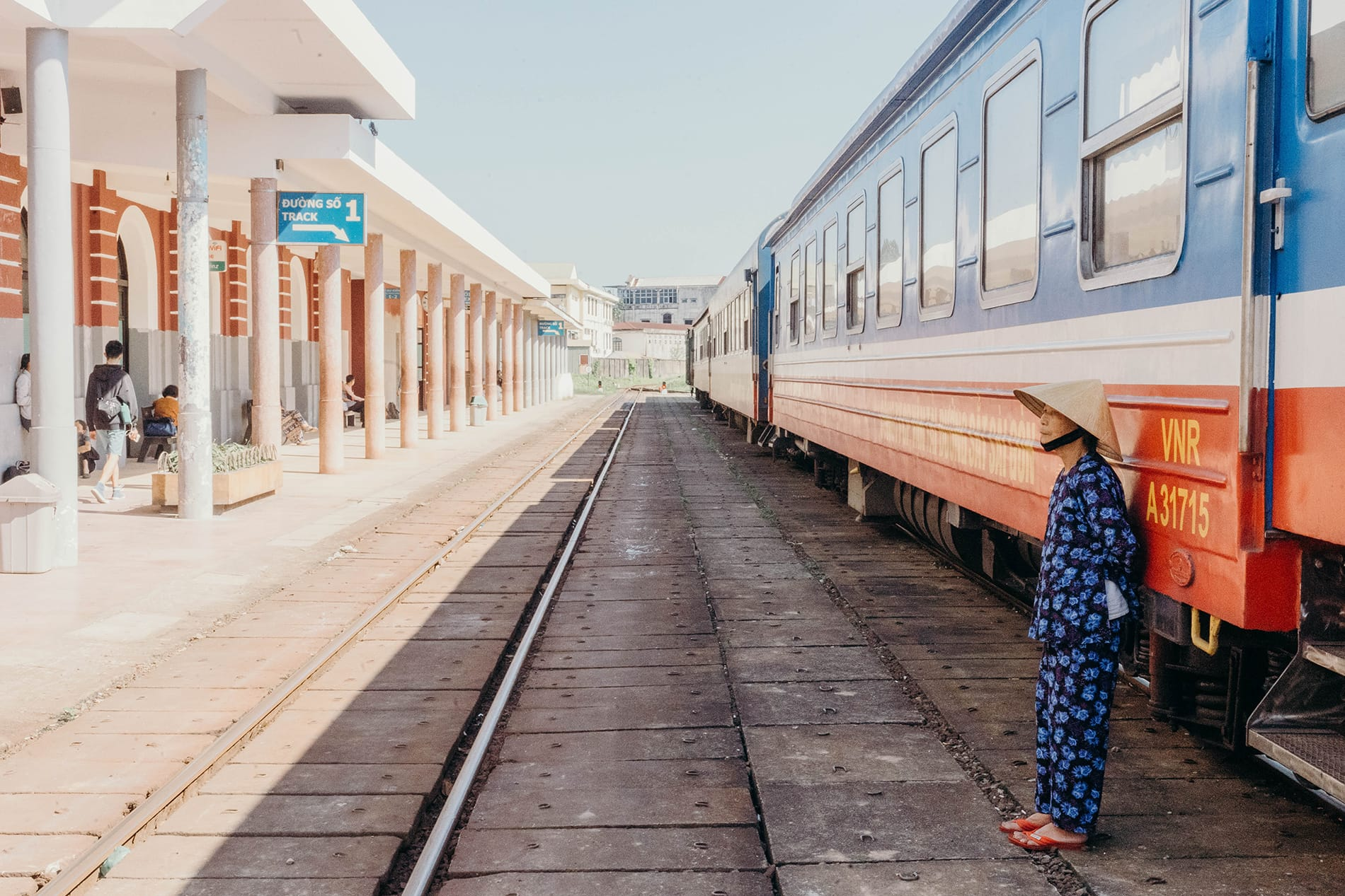 a vietnamese woman stands behind the train